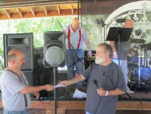 Bob Schmalzbach, president of the Happy Camp Chamber of Commerce presents Paul LaFleur with first prize won by The Flower Band at Rockin' the Klamath.